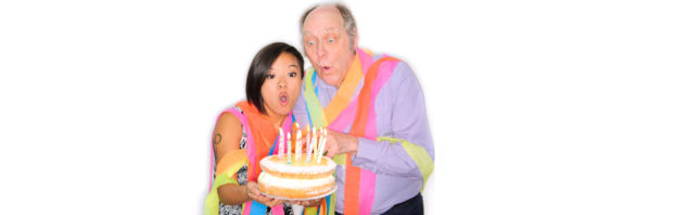 A man and a woman blow out the candles on a birthday cake.