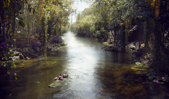 "Mowgli (newcomer Neel Sethi) and Baloo (voice of Bill Murray) float down a river in ""The Jungle Book"""